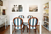 Striped chairs and fine-art photography in a dining room