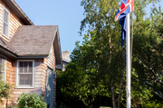 Flags fluttering in the wind outside a shingle-clad cottage