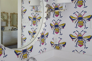Patterned wallpaper behind circle white rimmed mirror.