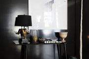 A tabletop vignette against a dark screen and wood flooring