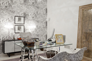 A glass desk and a pair of chairs against cloud-patterned wallpaper under a bubble chandelier