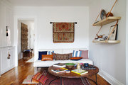 Boho chic living room with textile wall decor and colorful pillows.