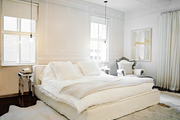 A neutral bedroom with white bedding and an upholstered bed layered atop multiple white hide rugs