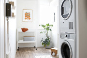 A washer/dryer in a hallway with a plant and small area rug.