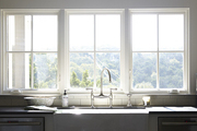 White framed windows above porcelain sink with silver faucet.