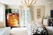 A brass chandelier, patterned bedding, and a blue upholstered bed in a sunny room