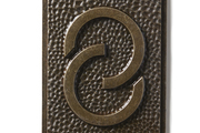 A bronzed door number created with a font by Frank Lloyd Wright