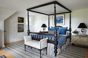An upholstered bench at the foot of an antique four-poster bed
