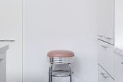 Single silver barstool below small framed art and white cabinets.