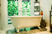 This is a clawfoot bathtub with a view outside.