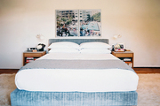 Art hung above a blue upholstered bed with white linens