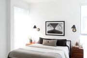 A contemporary bedroom with white walls and neutral decor.
