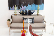 Artwork above a settee and 1970s cocktail table with a vintage airplane and midcentury glassware