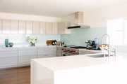 A sleek kitchen area with white counters, cabinets, and steel appliances.