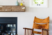 A leather rocking chair next to a rustic mantel