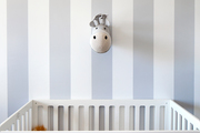 Striped walls and a white crib in a baby's room.