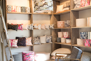 Variety of different patterns on throw pillows and lampshades in wood shelving.
