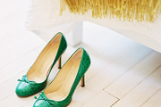 Green shoes sit on a white wooden floor next to a white quilt and wool throw blanket.