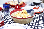A bread bowl with red, white, and blue dinnerware on a graphic tablecloth