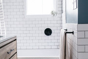 A contemporary bathroom with white tile and deep blue walls.