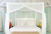 A four-poster bed with mosquito netting at La Banane