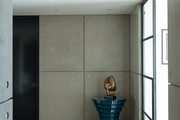 A sculpture on a table in an entry lined with concrete at the London home of designer Tara Bernerd