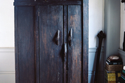 An antique armoire surrounded by stacks of books