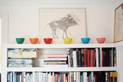 Multicolored bowls and framed artwork above a white bookcase