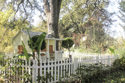 A kids playhouse surrounded by a picket fence
