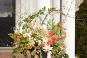 A footed urn of flowers beside white columns