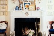 A leopard-print ottoman and wooden occasional chairs surrounding a white mantel