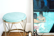 An upholstered stool next to a painting of two figures in a pool