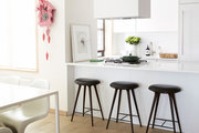 Contemporary bar stools in all-white kitchen.
