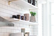 A contemporary kitchen with open shelving and white subway tile.
