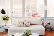 A square coffee table and a white settee in a light-filled living space