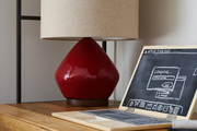 Red lamp and computer-shaped chalkboard on wood shelving.
