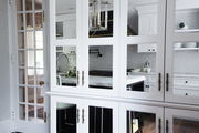 A floor-to-ceiling mirrored cupboard with vintage brass hardware in a glamorous kitchen