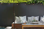 A green umbrella over a gray upholstered outdoor banquette in textile designer Bridgid Coulter's Los Angeles home