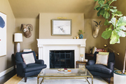 Two Barclay Butera armchairs flanking a fireplace with taxidermy and a fiddle-leaf fern