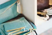 Turquoise and brown leather pouches and clutches on white shelves