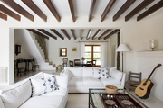 A living area with white sofas and exposed beams