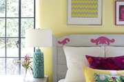 A colorful kids' room with casement windows and a bed topped by throw pillows