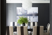 A white chandelier over a black dining table