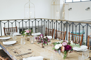 Natural wood dining table with floral arrangements in loft area.