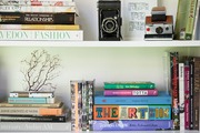 Colorful books and decor in white bookshelf.