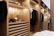 A full-length mirror in a dressing space equipped with wooden shelving and drawers offering many storage options