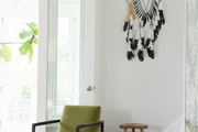An entryway with a feathered wall hanging and a green chair.