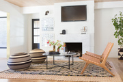 Living room with leather woven chairs and poufs.