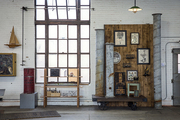 A wall of art pieces next to a loft-style window at American Street Showroom
