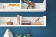 Floating shelves on blue accent wall complete with vintage sculptures and accent pieces.